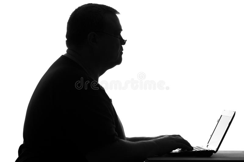 Silhouette of a plump man working at a laptop stock images