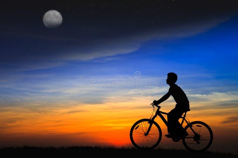 Silhouette pojken som rider en cykel på solnedgången royaltyfri bild
