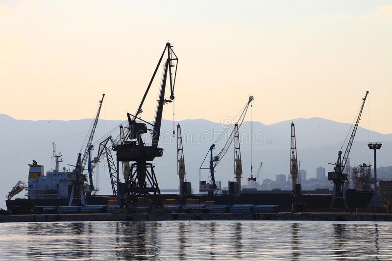 Silhouette of port cranes and ships, harbor of Rijeka, Croatia. Silhouette of port cranes and a bulk carrier ship in the harbor with Ucka mountain, Istria, in stock photography