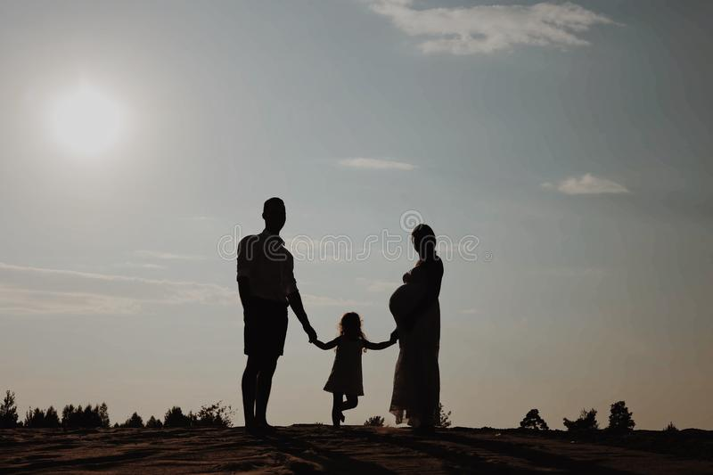 Silhouette portrait of beautiful young family in expectation of newborn. Man and woman standing face to face with their royalty free stock photos
