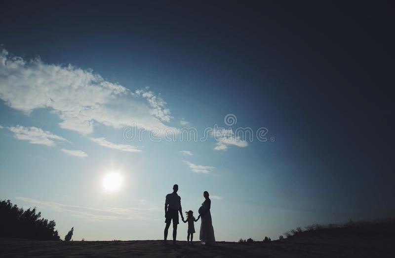 Silhouette portrait of beautiful young family in expectation of newborn. Man and woman standing face to face with their stock photo