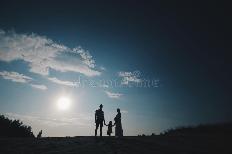 Silhouette portrait of beautiful young family in expectation of newborn. Man and woman standing face to face with their royalty free stock photography