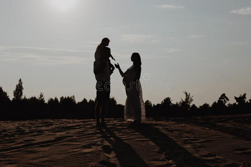 Silhouette portrait of beautiful young family in expectation of newborn. Man and woman standing face to face with their stock images
