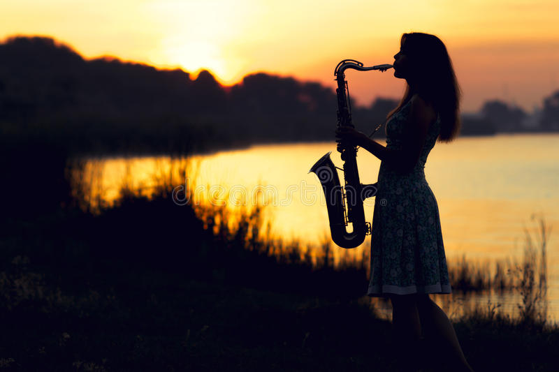 Silhouette portrait of a woman in a dress whose hobby music, she plays on the river bank and is resting emotionally stock photography
