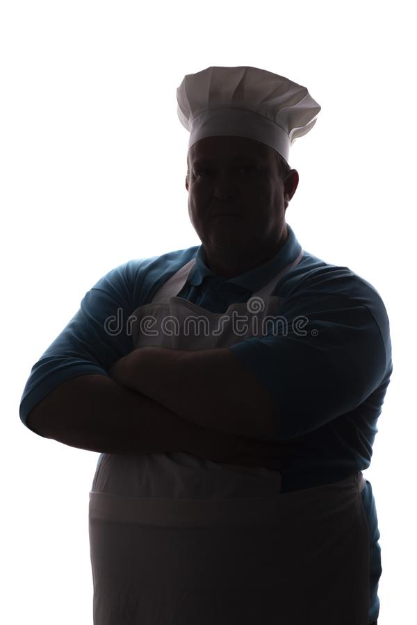 Silhouette of a pot-bellied good-natured funny chef in a hat, male cooker folded his arms over his chest on a white isolated backg royalty free stock photo