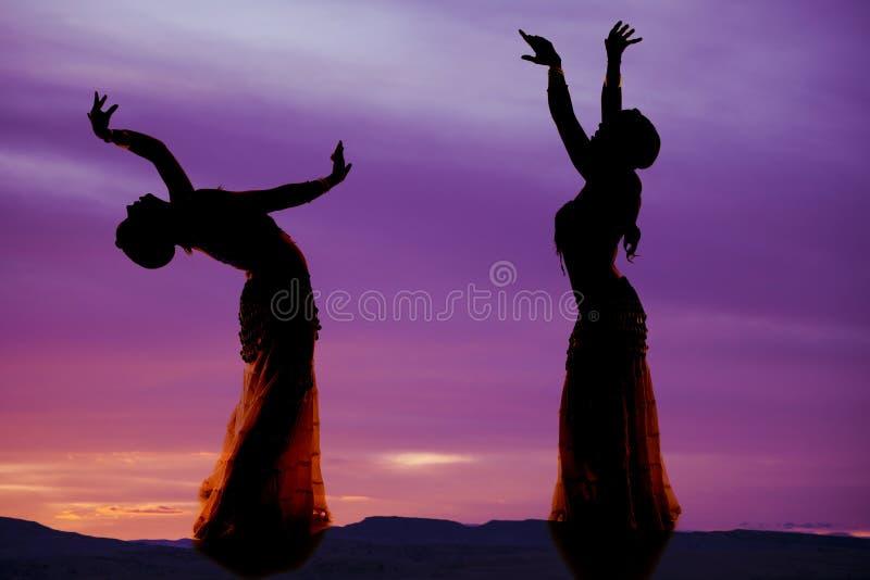 Silhouette pourpre deux de danseuse du ventre image libre de droits