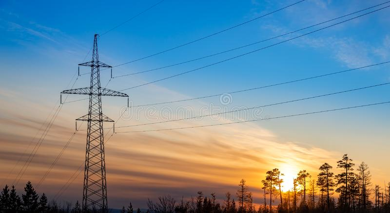 Silhouette of power lines at sunset. In a forest area royalty free stock photos
