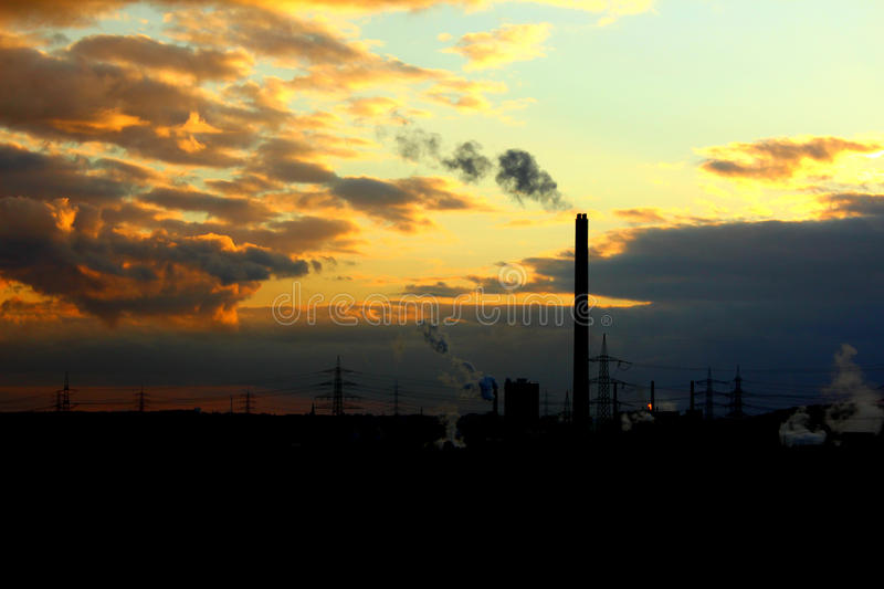 A silhouette of a power plant with a high smoking chimney at a s. Unset stock image