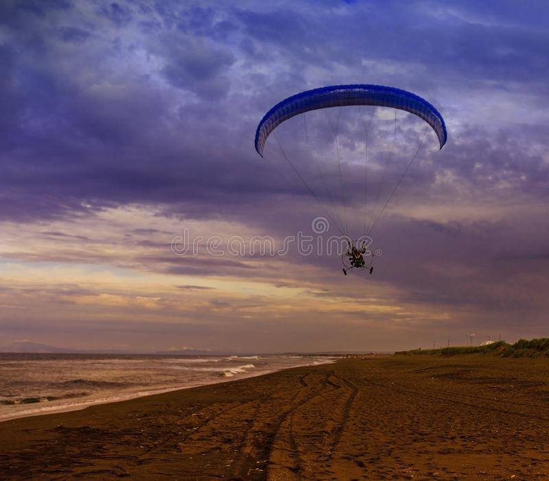 The Silhouette of powered paraglider soaring flight over the sea against sunset sky stock photos