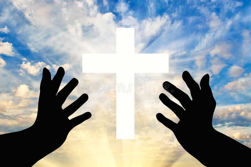 Silhouette of praying hands and a cross. Concept of religion. Silhouette of praying hands and a cross against a beautiful sky stock photos