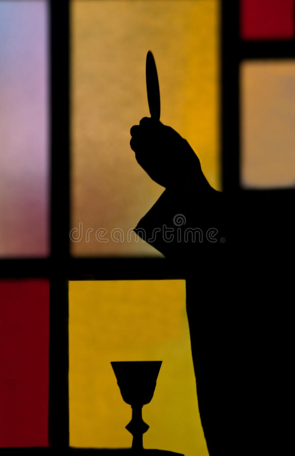 Silhouette of priest lifting host. Silhouette of a priest lifting the wafer or host during catholic mass royalty free stock image