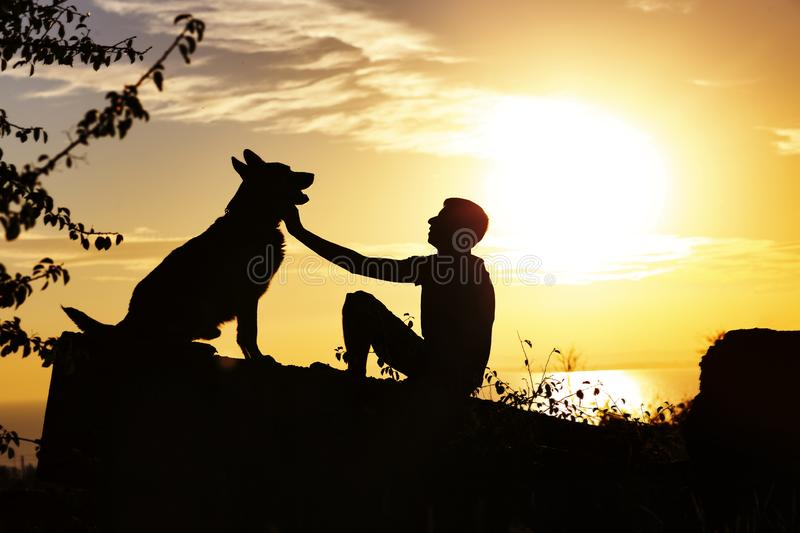 Silhouette profile of man and dog sitting in front of each other on nature, boy caress his pet at sunset in a field, concept royalty free stock images