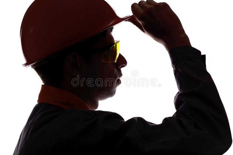 Silhouette profile of a man face construction engineer in helmet and protective glasses on a white isolated stock photography