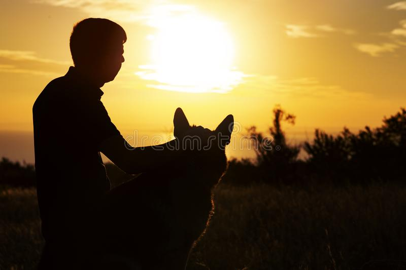 Silhouette profile of a young man and a dog watching the sun set on the horizon in a field, boy fondle his pet on nature, concept royalty free stock photo