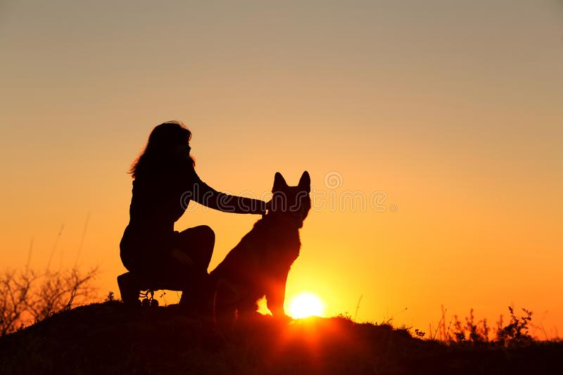 Silhouette profile of young woman embracing German Shepherd dog obediently sitting nearby, girl walking on nature with pet. Enjoying sunset in a field, concept royalty free stock photography