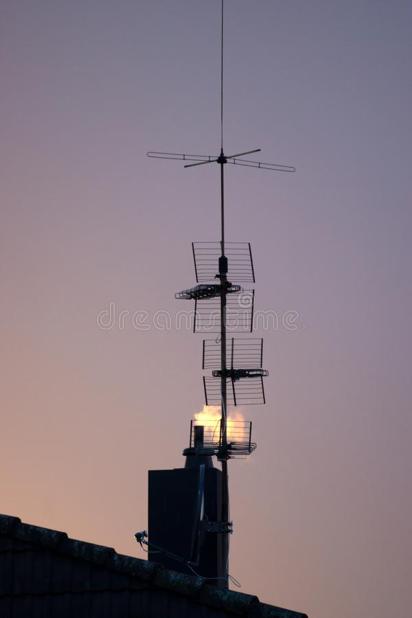 Silhouette of radio and TV antennae in front of smoking chimney. And evening sky royalty free stock photos