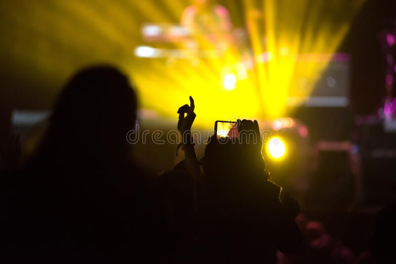 Silhouette of raised hands holding a smart phone recording music concert. Stage lights in the background royalty free stock photos