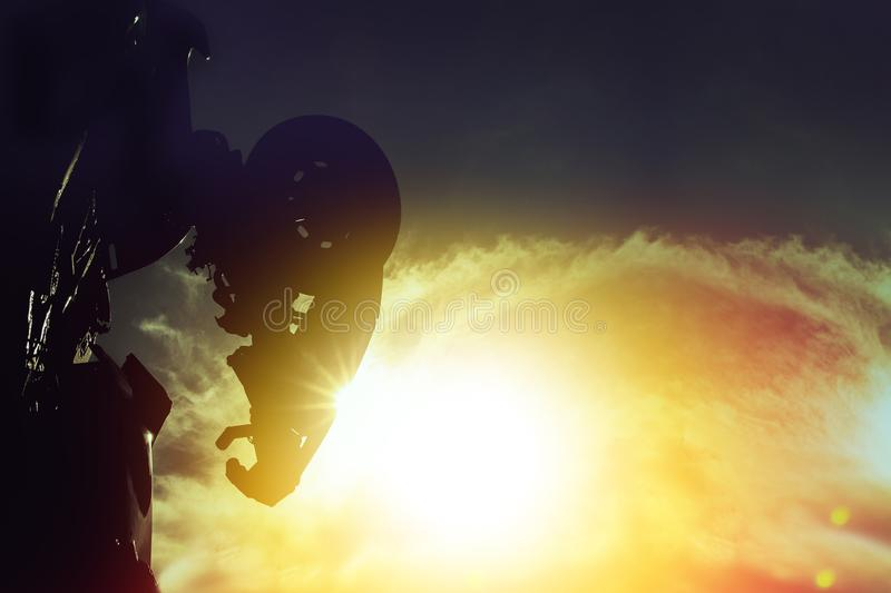 Silhouette rear of metal robot standing in sunset sky stock images