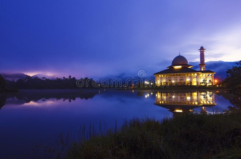 Silhouette and reflection of mosque over magical sunrise stock image