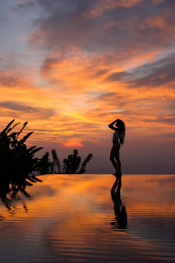Silhouette and reflection of slim woman on edge infinity luxury pool at sunset. Silhouette and reflection of woman with ideal figure on edge infinity luxury pool royalty free stock image