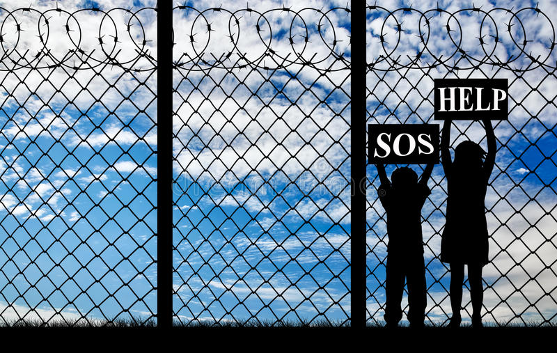 Silhouette of refugee children. Concept of refugee. Silhouette of refugee children with placards in their hands asking for help near the fence stock image