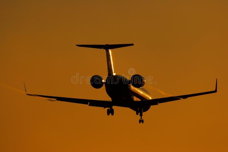 Silhouette of regional jet facing sun stock photography