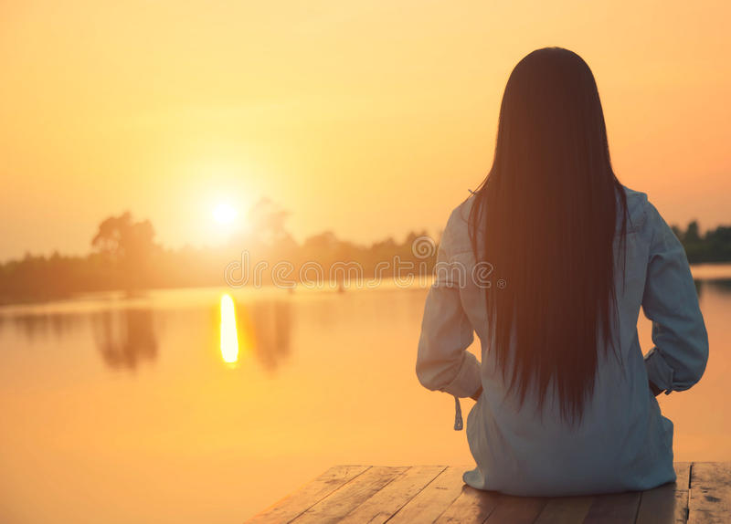Silhouette of relaxing young woman on wooden pier at the lake in sunset royalty free stock images