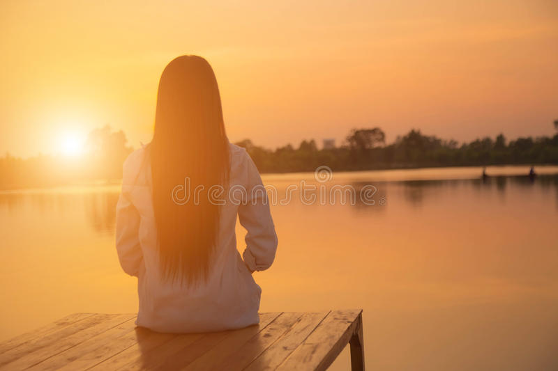 Silhouette of relaxing young woman on wooden pier at the lake in sunset royalty free stock photography