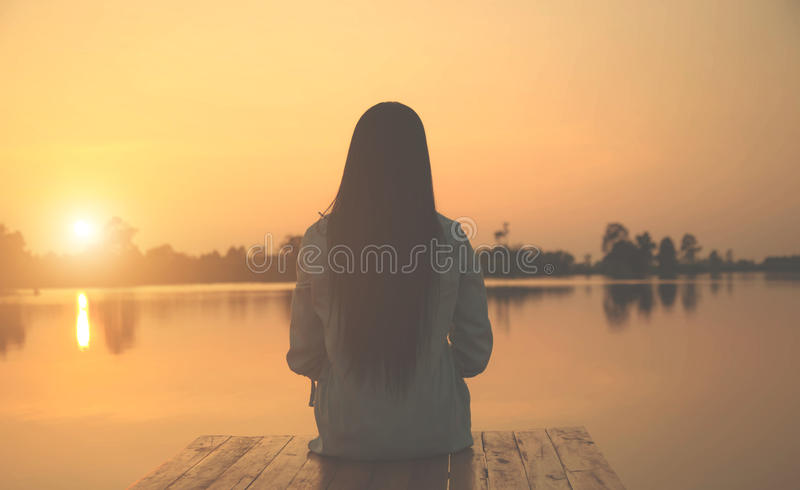 Silhouette of relaxing young woman on wooden pier at the lake in sunset royalty free stock photo