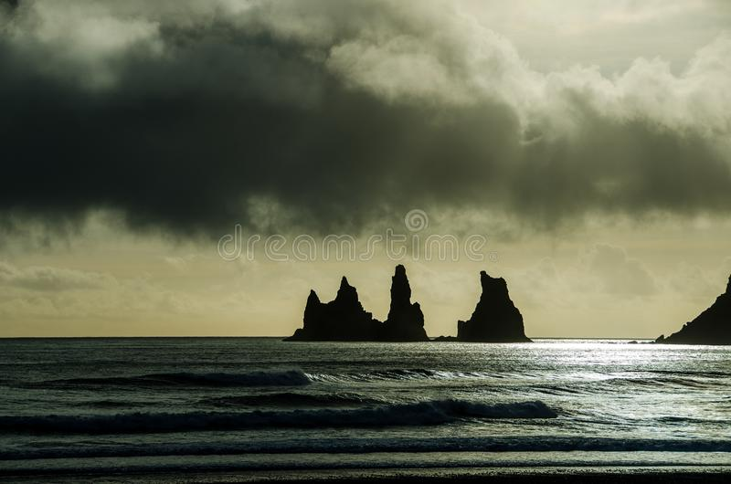 Storm clouds over Reynisfjara rock stacks in Iceland stock photos