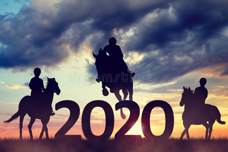 Silhouette of a riders riding a horse in the sunset. New Year 2020 concept. stock photo