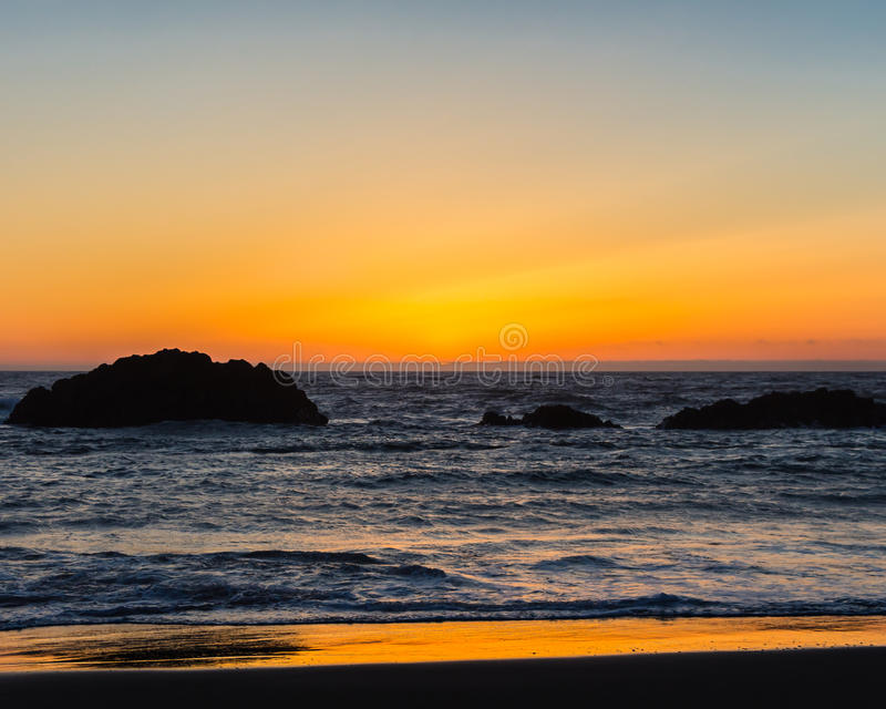 Silhouette of rocks at sunset Lincoln City Oregon stock photo