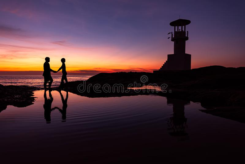 Silhouette Romantic couple with lighthouse at sunset time on background.  stock photo