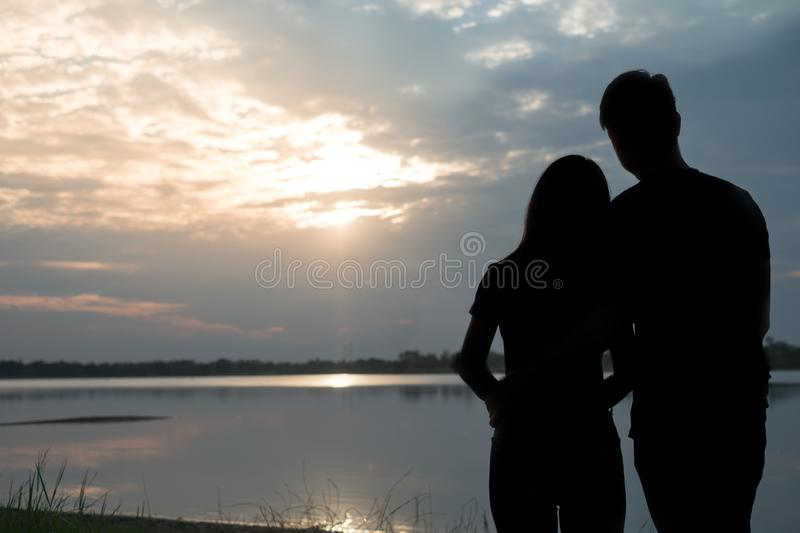 The silhouette of a romantic couple standing, hugging each other and watching the sunset. Romance and love concept stock photography