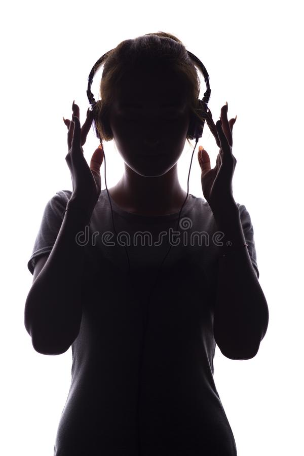 Silhouette of a romantic girl listening to music in headphones, young woman relaxing on a white  background, concept of stock photography