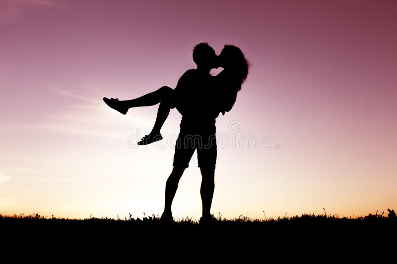 Silhouette of romantic lovers with sunset on the back stock photography