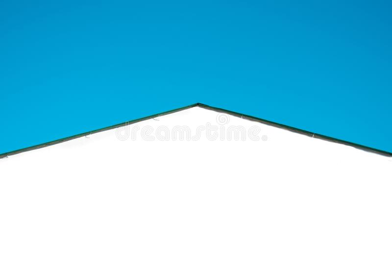 Silhouette of a roof of a white house and the sky stock photography
