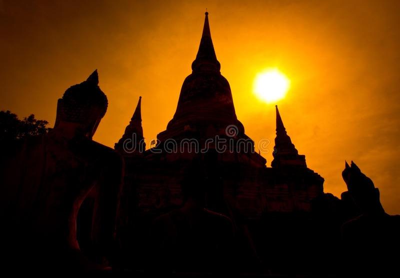 Silhouette ruined pagoda and Buddha statue, Thailand. Ruined pagoda and Buddha statue at Wat Yai Chai Mongkon in Ayutthaya province of Thailand royalty free stock photo