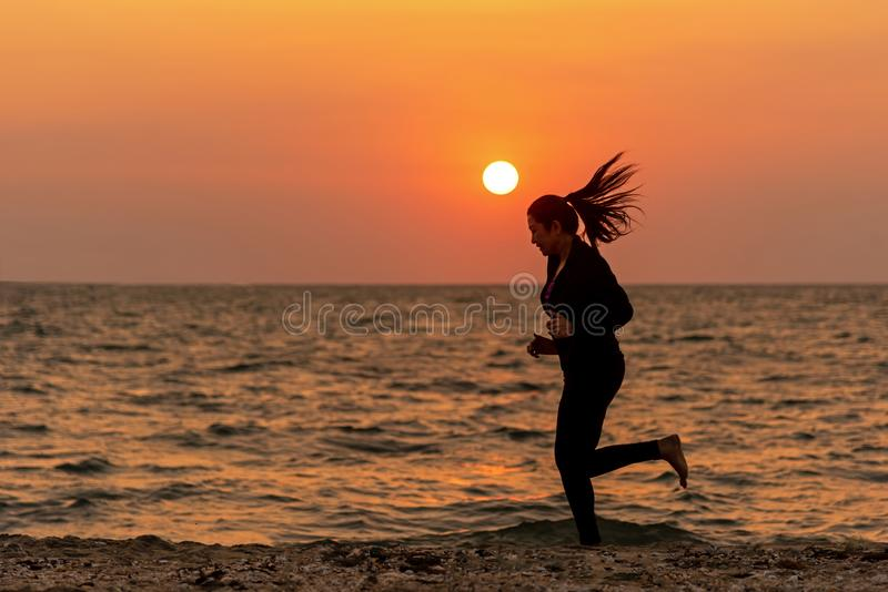Silhouette runner feet running on the beach in the sunset outdoor. Asian fitness and sporty woman running for healthy and relax. royalty free stock photography