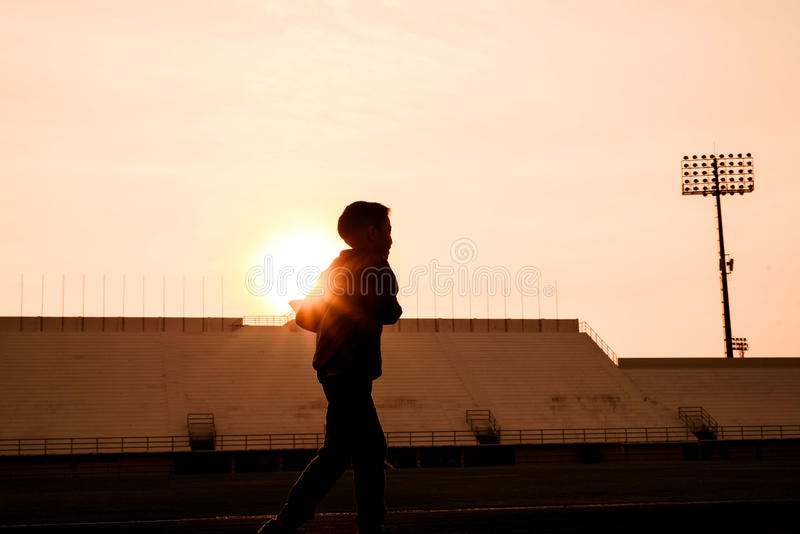 Silhouette Running boy. Silhouette Young boy in blue jacket running on track in the stadium against sunrise to practice himself royalty free stock images