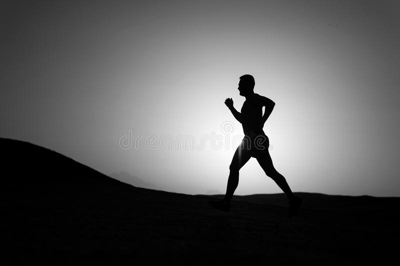 Running man silhouette at sunset sky stock photography