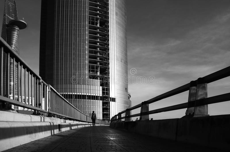 Silhouette's lonely people walking on the way to highrise buidl. Ing of modern city, the person become tiny with high building royalty free stock photos