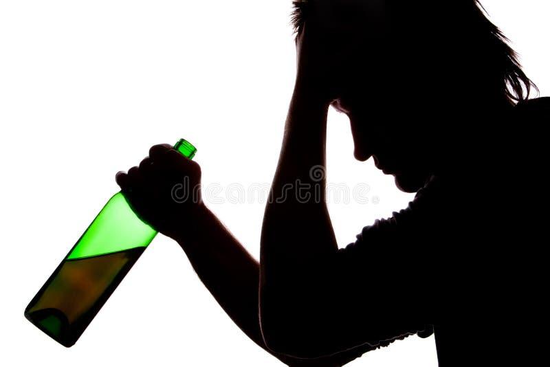Silhouette of sad man drinking alcohol stock image