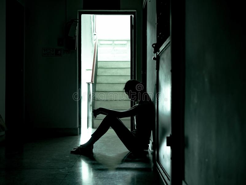 Silhouette of a sad young girl sitting in the dark leaning against the wall, Domestic violence, family problems, Stress, violence royalty free stock images