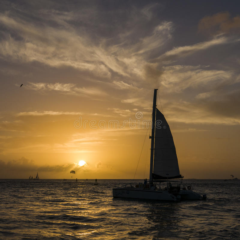 Silhouette of sailboat during vibrant sunset stock photo