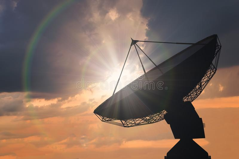Silhouette of satellite dish or radio antenna at sunset.  stock photo