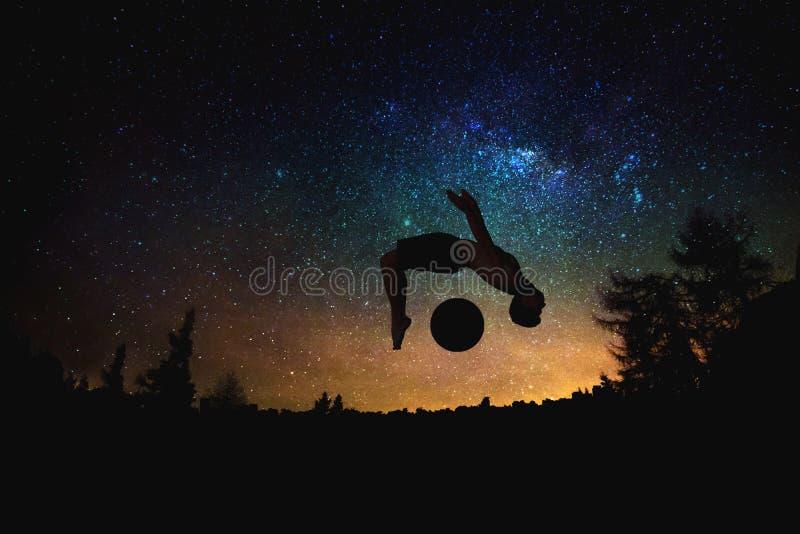 Silhouette sautante d'homme sportif au fond étoilé de ciel et de lune de nuit photographie stock