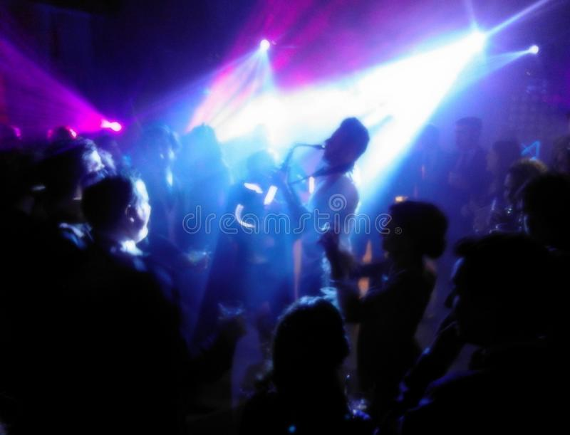 Silhouette of a saxophonist surrounded by a lot of people under the spotlights stock images