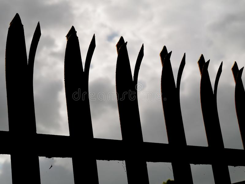 Silhouette of a security anti climbing fence. Dramatic dark cloudy sky. Concept safety measures stock image