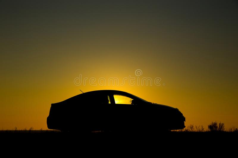 Silhouette of sedan car on the background of sunset. Silhouette of sedan car on the background of beautiful sunset royalty free stock photo